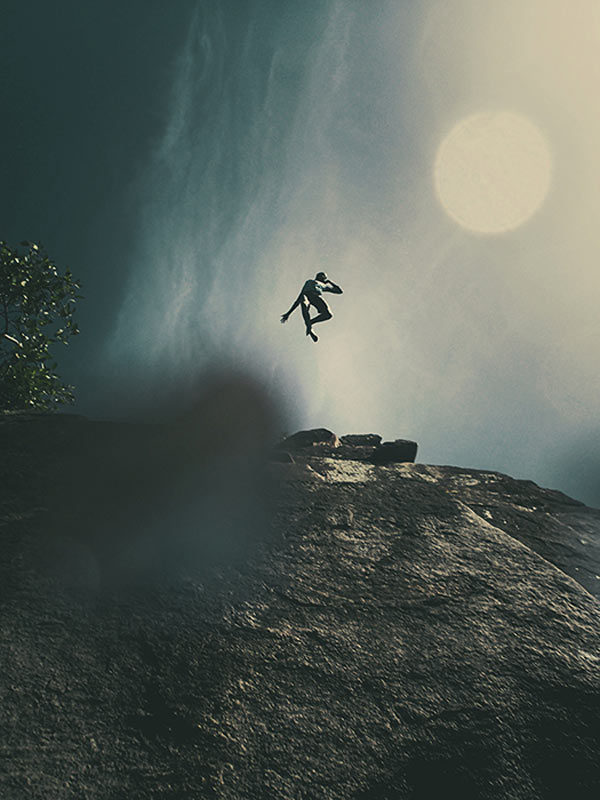 A boy is jumping from a steep cliff.