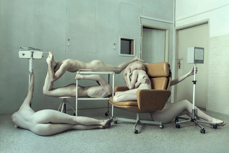Naked performers posing in choreographed positions.
