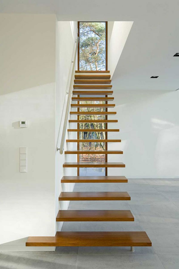 A seemingly floating staircase leads to the upper floor.