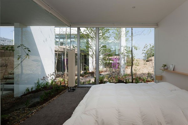 The bedroom - glass facades allow views of the garden.