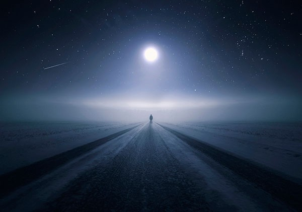 Standing on a lonely road that follows the moon.