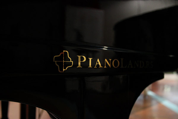 Golden logotype on the black piano.