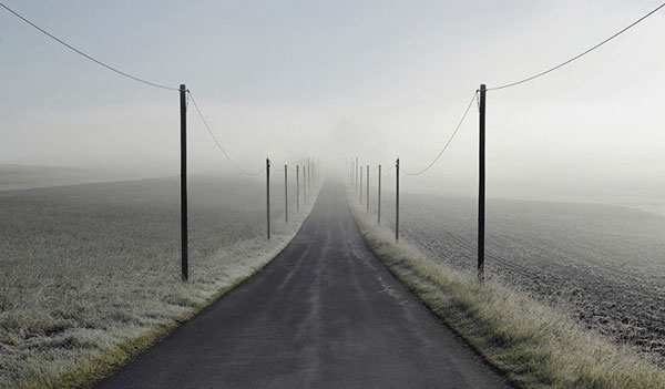 A solitary, straight road leads directly into the fog.