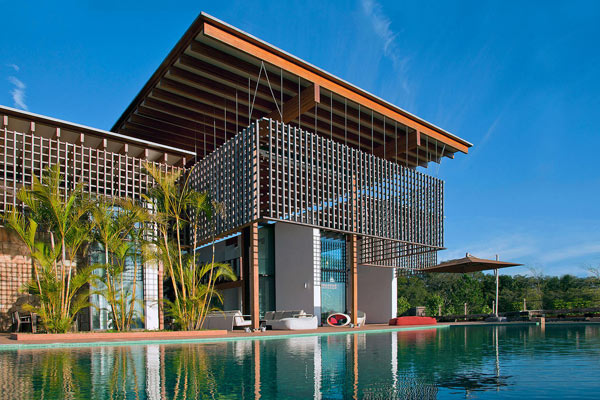 View from the pool to the house with the sun filtering wood lattice panel.