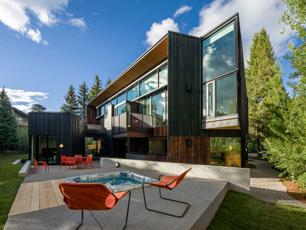 The house is characterized by modern architectural design, a wooden paneling, and large windows to the front.