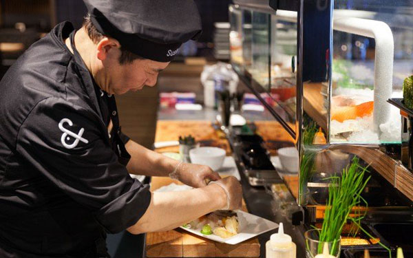 The sushi chef at the delicate preparation.