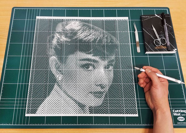 The artist at work, Yoo Hyun carves a stunning paper portrait of Audrey Hepburn by hand.