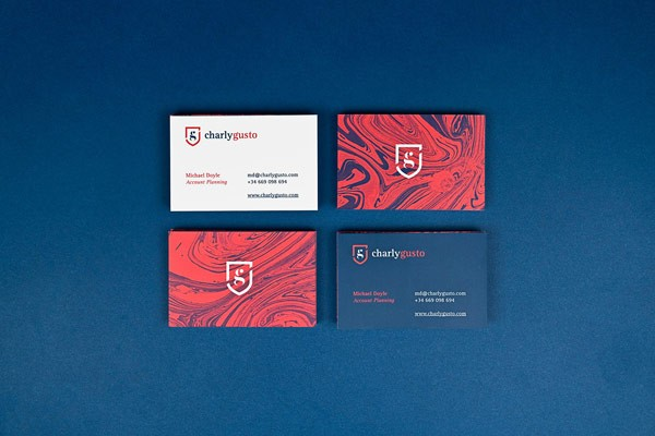 Business cards for Charly Gusto, a marketing professional with a British origin.