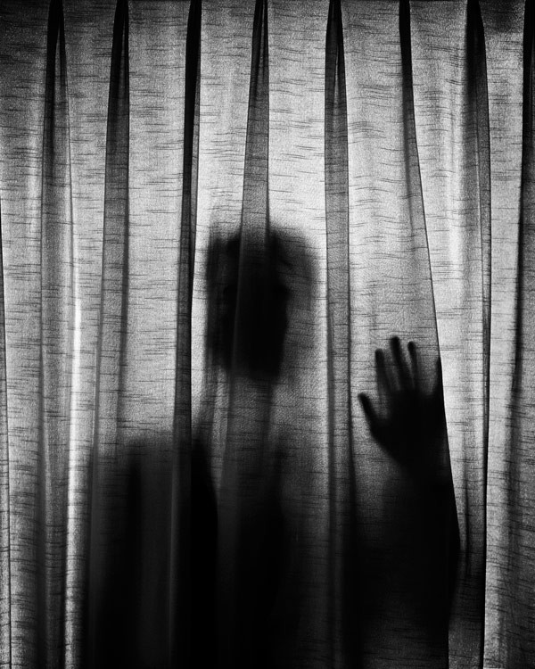 Just a silhouette behind the curtain. A photo from a series of self-portraits by Edward Honaker.