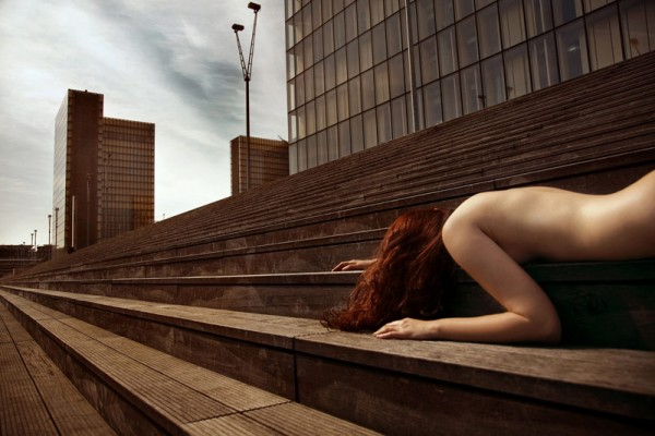 Lying down on the stairs in a public environment.