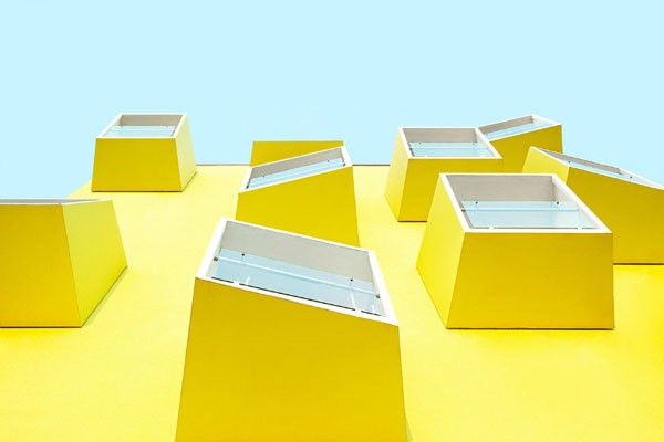 Modern architecture – yellow house facade with protruding windows.