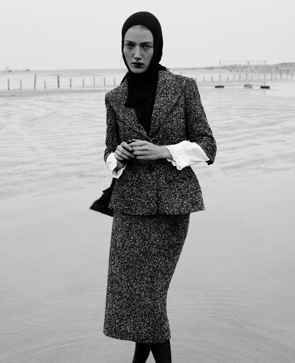 Model Lou Schoof is posing at the beach for a series of black and white fashion photographs.