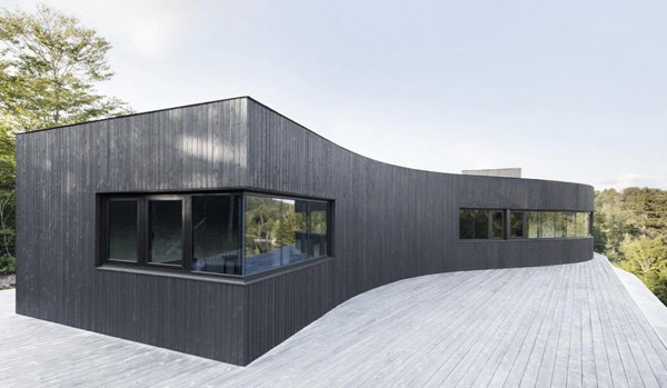 The facade of the house is clad with black wooden slats.