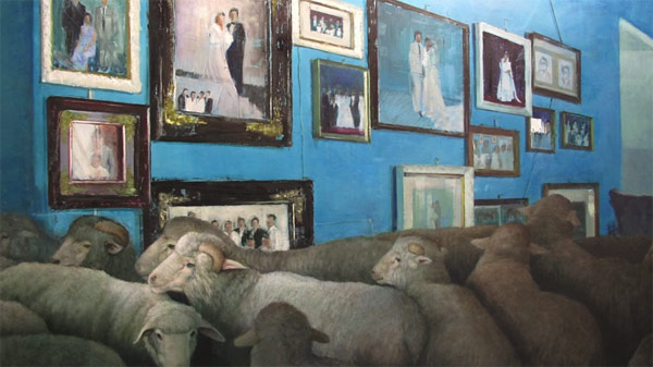 Sheeps in front of a wall of paintings.