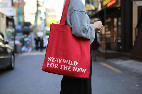 A red cloth bag with printed quote.