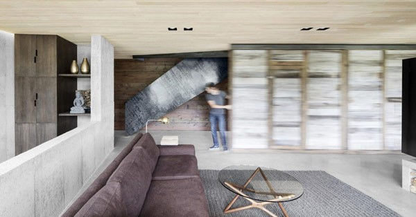 A movable wall separates the living room from the staircase.