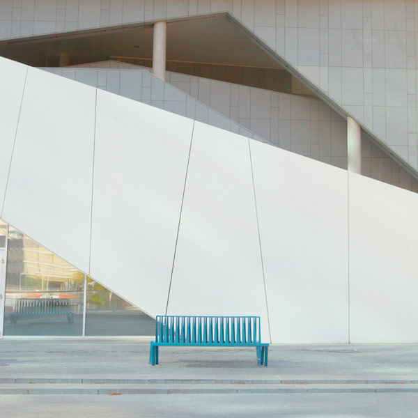 A bench in front of edgy architectural shapes.