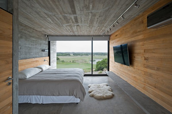 This bedroom has a floor to ceiling window as well as a wood-paneled wall to create a contrast to the concrete walls.
