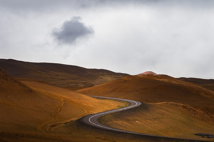 A winding road embedded in a beautiful hilly landscape.