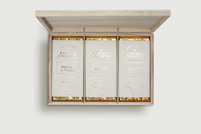 The wood box includes delicious chocolates wrapped in golden paper.