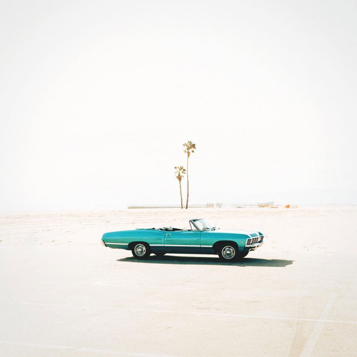 The photo of the old Chevrolet Impala in front of the palm tree has been taken by Garrett Cornelison at Venice Beach.