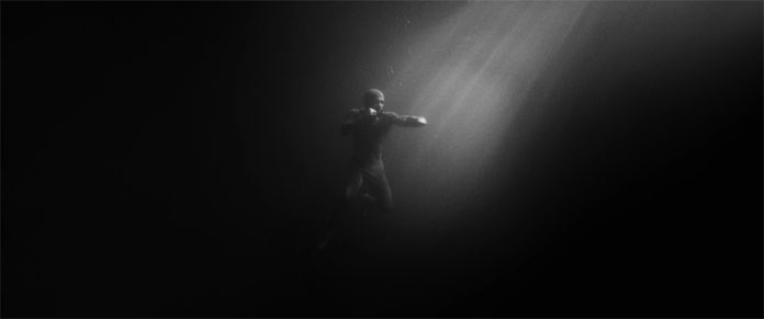 Amazing underwater scene showing the man free-floating in the water, boxing in a spotlight.