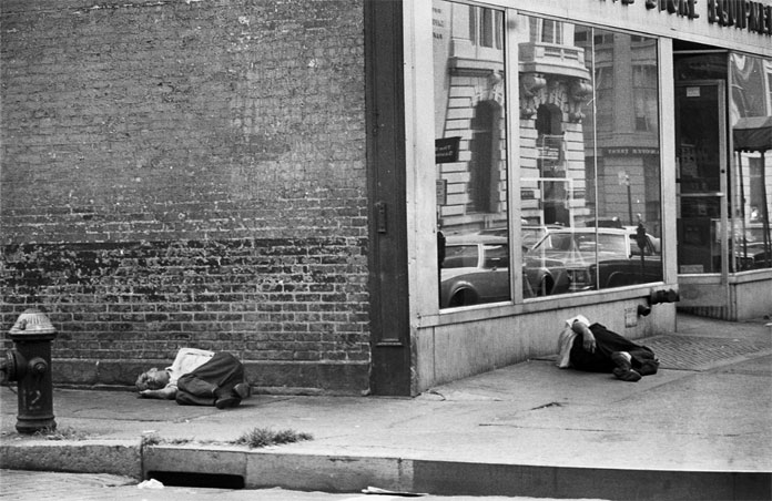 Homeless people lying on the ground.