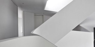 The space is characterized by the curvilinear forms of the staircase and the different floors.