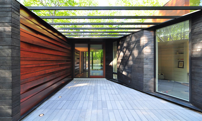 The entrance of the house was enhanced by a wall of wood slats, which have been stacked at slight angles.