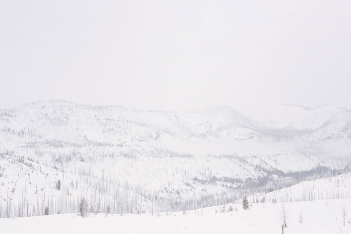 A snowy mountain setting in front of a cloudy sky shot by Photographer Sam Barker.