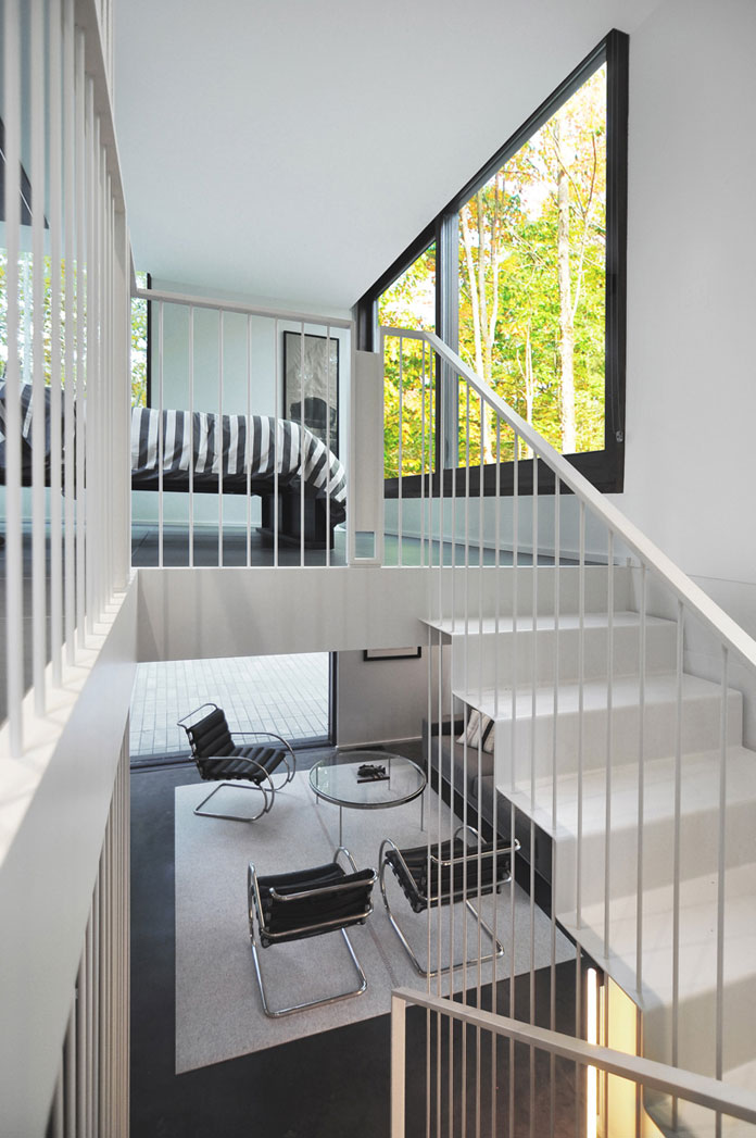 A steel staircase with vertical rods leads from the living area up to the bedroom.