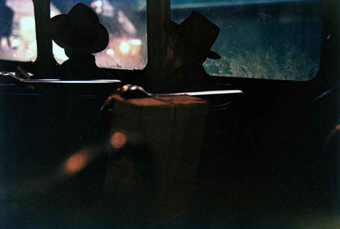 Two men in hats on train at night photographed by Saul Leiter.