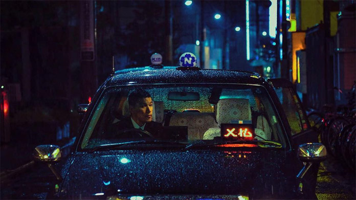 A taxi driver waits in the rain for a couple, which has some fun in the love hotel.