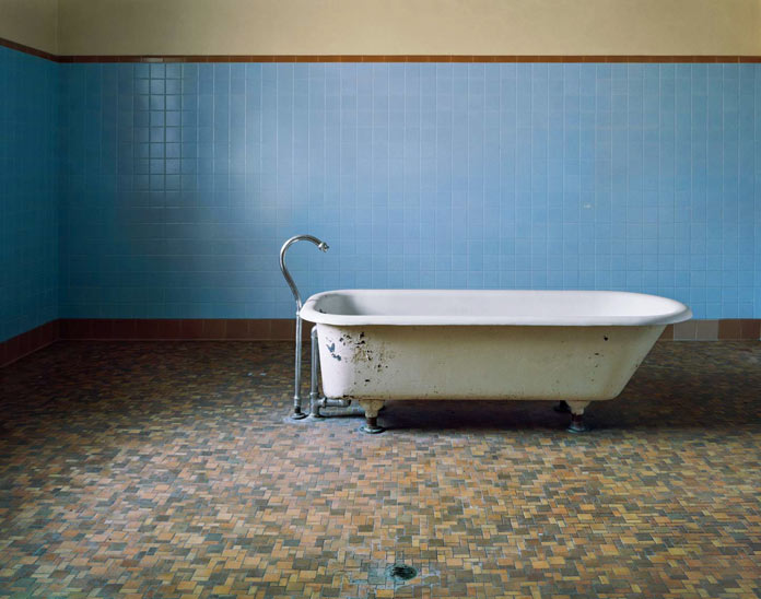 A bathtub in an almost empty room.