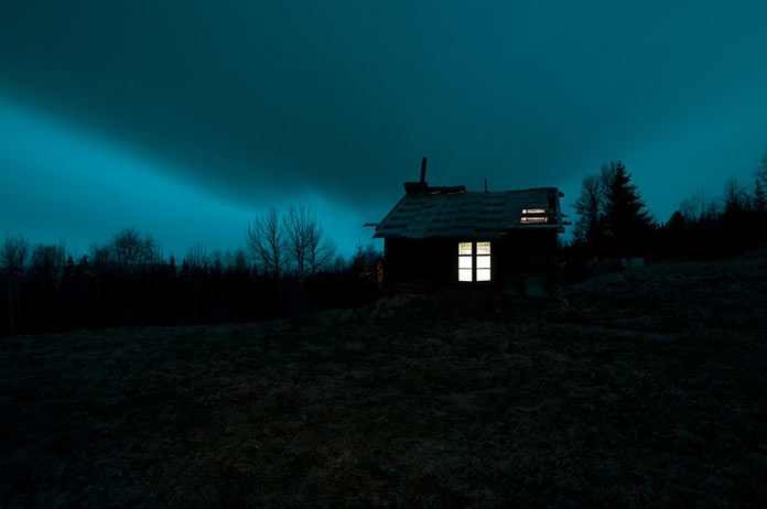 A secluded cabin in front of a gloomy sky.