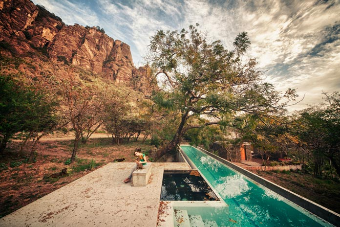 The pool is nestled in a natural environment.
