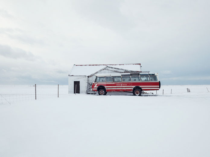 A lonesome red bus in the snow.