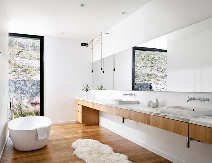 Modern white bathroom design with wood segments.