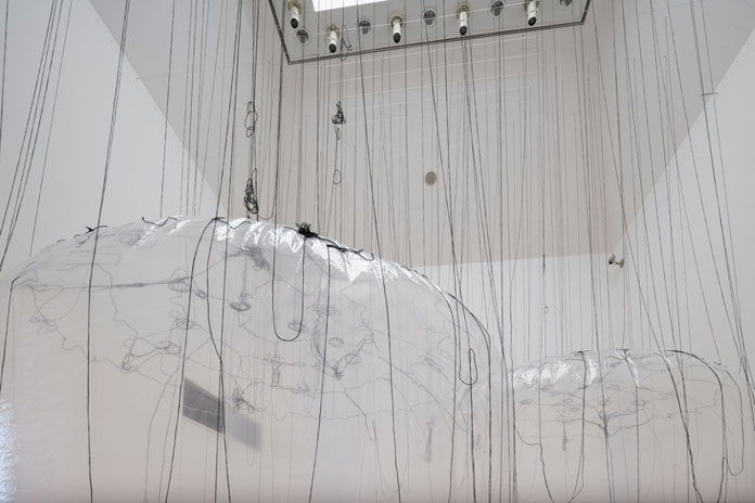 Yasuaki Onishi, attached to the ceiling with numerous threads.
