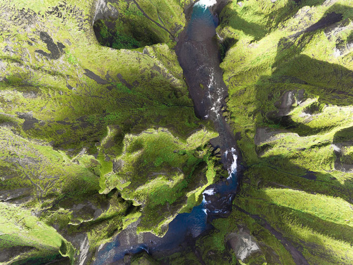 Iceland from above - aerial photography by Kevin Krautgartner, green mountains and a river.