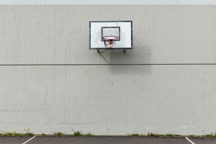 A basketball net attached to a concrete wall.