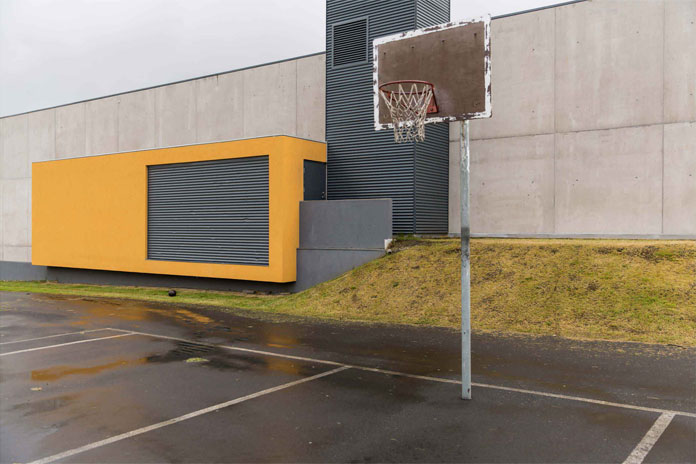 A basketball net on a parking space.