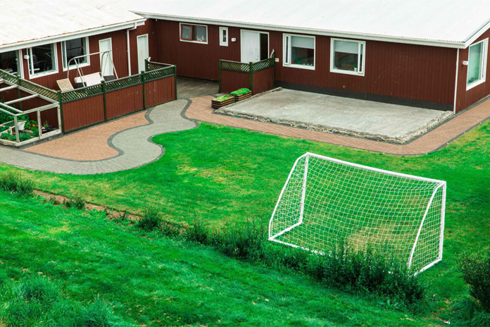A neatly arranged backyard with soccer field and a winding path.