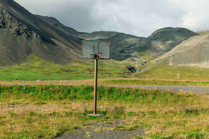 An abandoned basketball in front of the mountains.