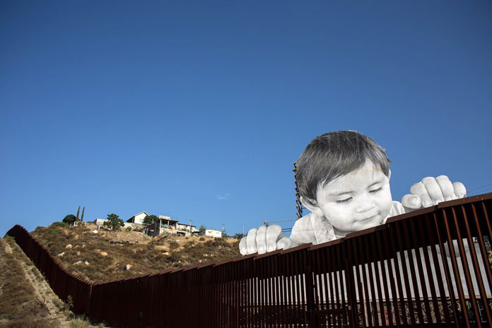 The nearly 70-ft tall image creates the illusion of a child that's looking over the frontier wall.