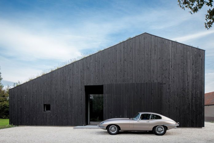 Minimalist architecture with black, wood-clad walls.